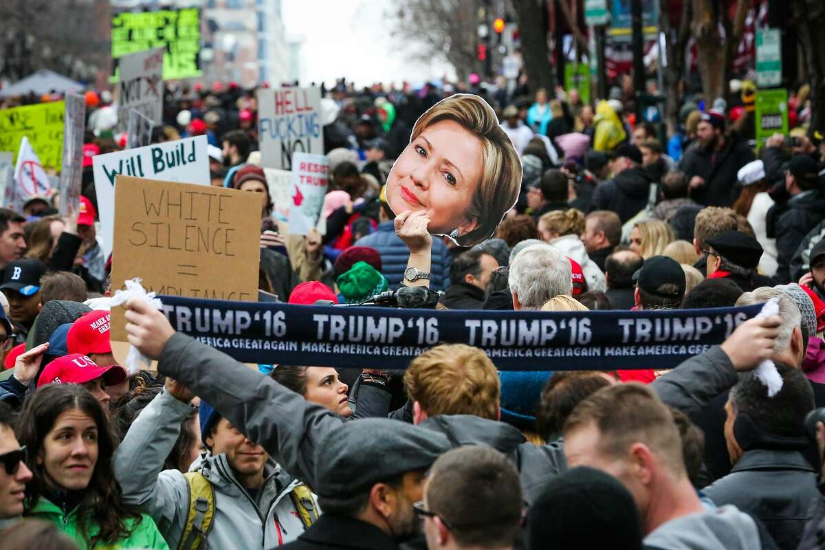 Anti-Trump protesters hold up signs as a Trump supporter (right) holds up his Trump scarf during a protest after the Presidential inauguration on D Street in Washington, D.C., on Friday, Jan. 20, 2017.