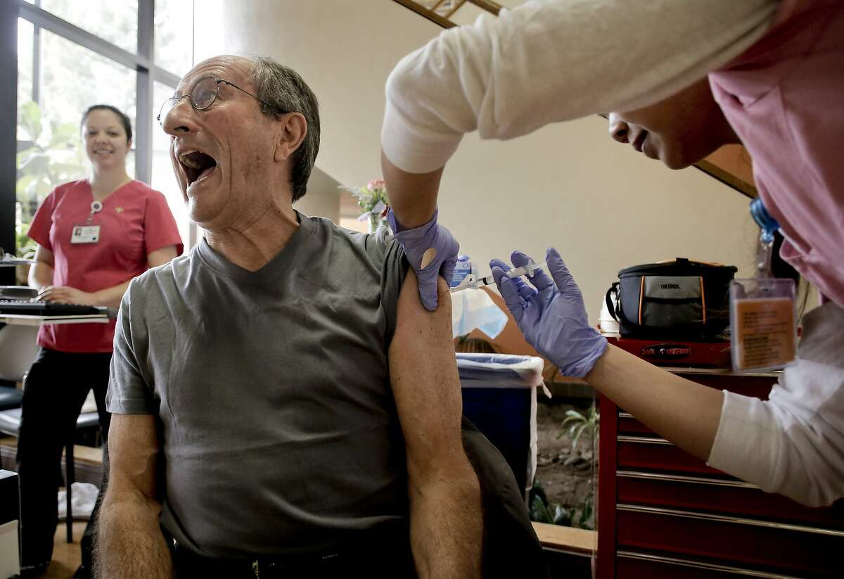 Pascal Jean Pierre, of Menlo Park, plays it up as he gets a flu shot from Ginny To, a LVN at the Kaiser Permanente flu clinic in Redwood City, Calif., on Thursday Dec. 18, 2014. Kaiser has already administered over one million flu shots in their Northern California facilities.