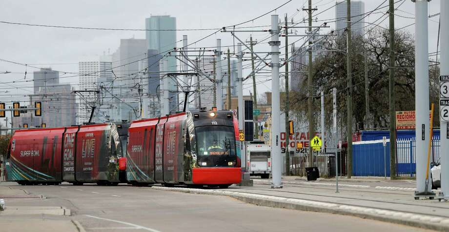 A Metro  train branded for Super Bowl LI cuts across Harrisburg as it made it's way across the recently completed Harrisburg Overpass Bridge, with downtown Houston in the background on Jan. 9.  Especially in the downtown area and along the Red Line to NRG Park, the trains will handle tens of thousands of trips related to the Super Bowl and associated events. Photo: Karen Warren, Staff Photographer / 2016 Houston Chronicle