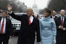 President Donald Trump waves as he walks with first lady Melania Trump during the inauguration parade on Pennsylvania Avenue in Washington, Friday, Jan. 20, 2016.
