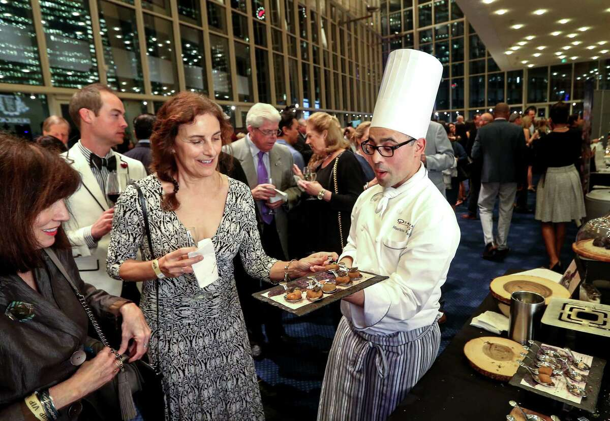 Maurizio Ferrarese, executive chef at Quattro at the Four Seasons, left, offers truffles to Susan Backes, center, and Karen Kislingbury, left, at Truffle Masters 2017, at the Hobby Center, Monday, Jan. 16, 2017, in Houston. ( Jon Shapley / Houston Chronicle )