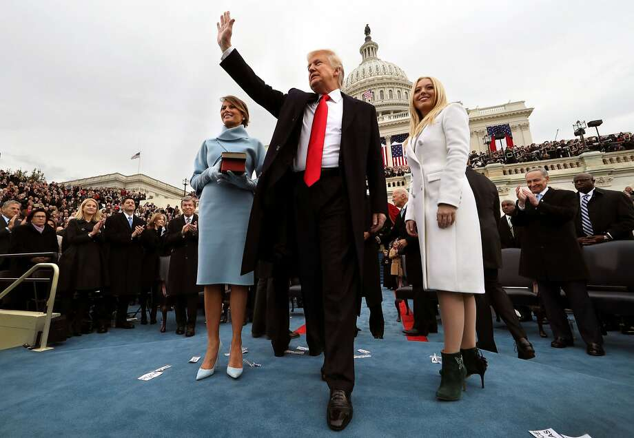 President Trump, with first lady Melania holding a Bible and daughter Tiffany at his side, waves after taking the oath of office. Photo: Jim Bourg, Associated Press
