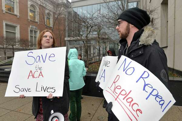 Molly Brechtel, at left, and Daniel Doubet join about 15 protestors gathered at the Federal Courthouse in Erie, Pa., on Thursday, Jan. 12 to deliver signatures to U.S. Sen. Pat Toomey, R-Pa., who has an office at the courthouse. The protestors urged Toomey not to repeal the Affordable Care Act without a replacement.