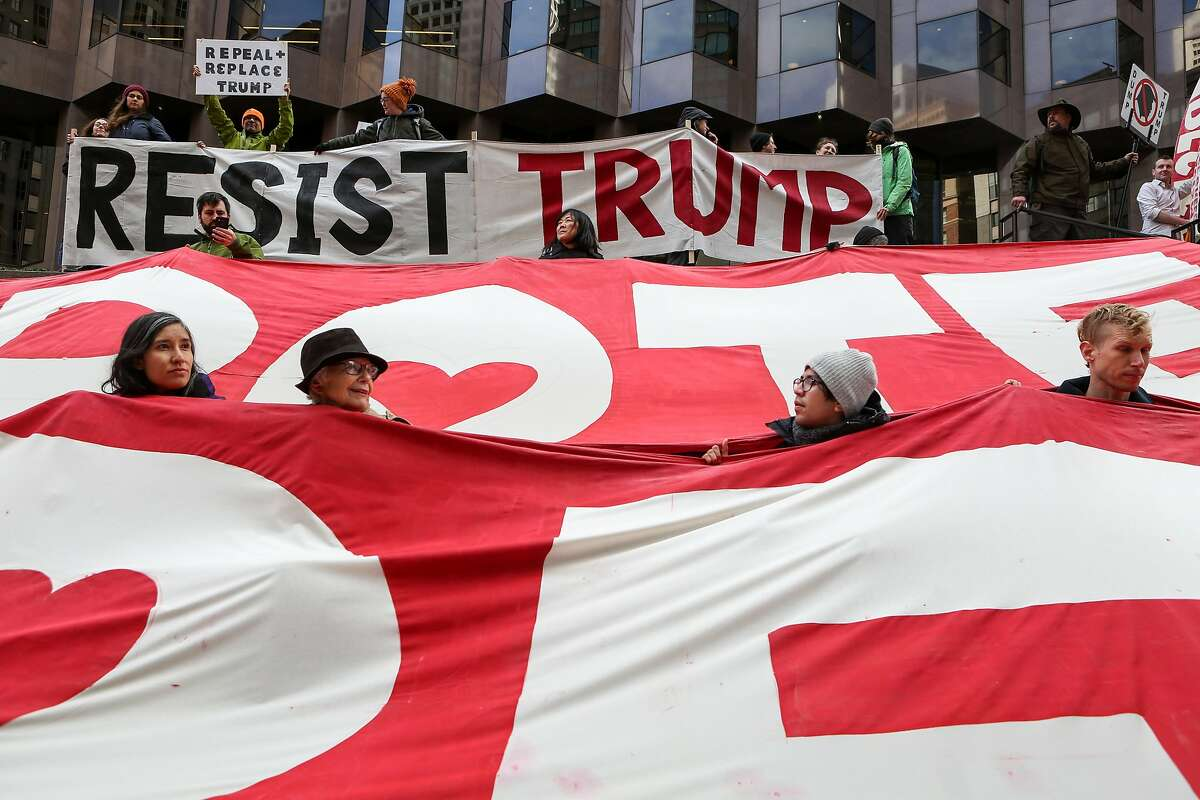 Demonstrators hold an anti-trump banners at 555 California St on Friday, January 20, 2017 in San Francisco, Calif.
