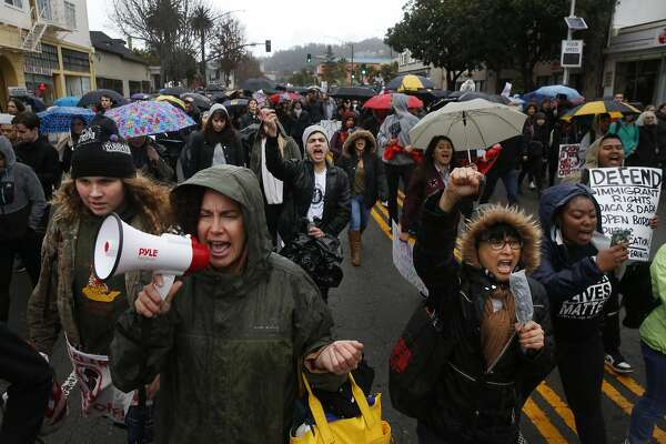 """Protesters march down Telegraph Ave. during a planned """"J20"""" walk-out protest in response to the inauguration of President Donald J. Trump Jan. 20, 2017 in Oakland, Calif."""