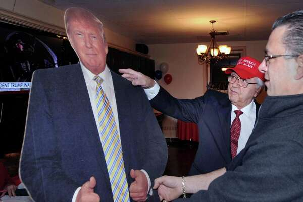 Anthony DeVita, left, pats a President Donald Trump cut-out figure on the shoulder as Mark Longo holds it up during the President Trump Inauguration party at the St. Lawrence Society in the Cos Cob section of Greenwich, Conn., Friday night, Jan. 20, 2017. Both men are Greenwich residents and Longo is a vice president at the club.