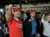 Asher Warriach, left, and Sonny Khatua, center, cheer during the GOP inaugural watch party at Ninfa's, 2704 Navigation Blvd., Friday, Jan. 20, 2017, in Houston. ( Melissa Phillip / Houston Chronicle )