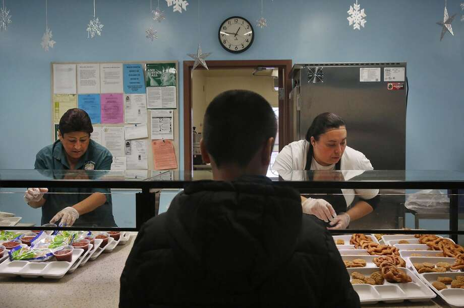 Monica Rocha, assistant manager for child nutrition (left) and Jenny Lopez, a certified nursing assistant, serve lunch in the cafeteria at Stoneman Elementary School in Pittsburg. Photo: Leah Millis, The Chronicle