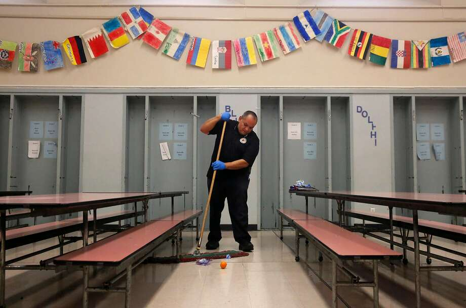 Head custodian Adam Zendejas sweeps the cafeteria floor as quickly as possible between two groups of students during lunchtime at Stoneman Elementary School Jan. 12, 2017 in Pittsburg, Calif. Photo: Leah Millis, The Chronicle