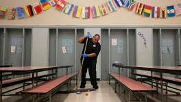 Head custodian Adam Zendejas sweeps the cafeteria floor as quickly as possible between two groups of students during lunchtime at Stoneman Elementary School Jan. 12, 2017 in Pittsburg, Calif.