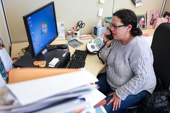 Resource navigation manager, Ellen Novogrodsky, makes a phone call to California Department of Public Health at SF AIDS Foundation on Thursday, January 19, 2017 in San Francisco, Calif.