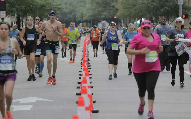 Marathon runners, left, and half-marathon runners, right, make their way down Lamar Street for the final miles on Jan. 15, 2017, in Houston.  (Elizabeth Conley / Houston Chronicle )