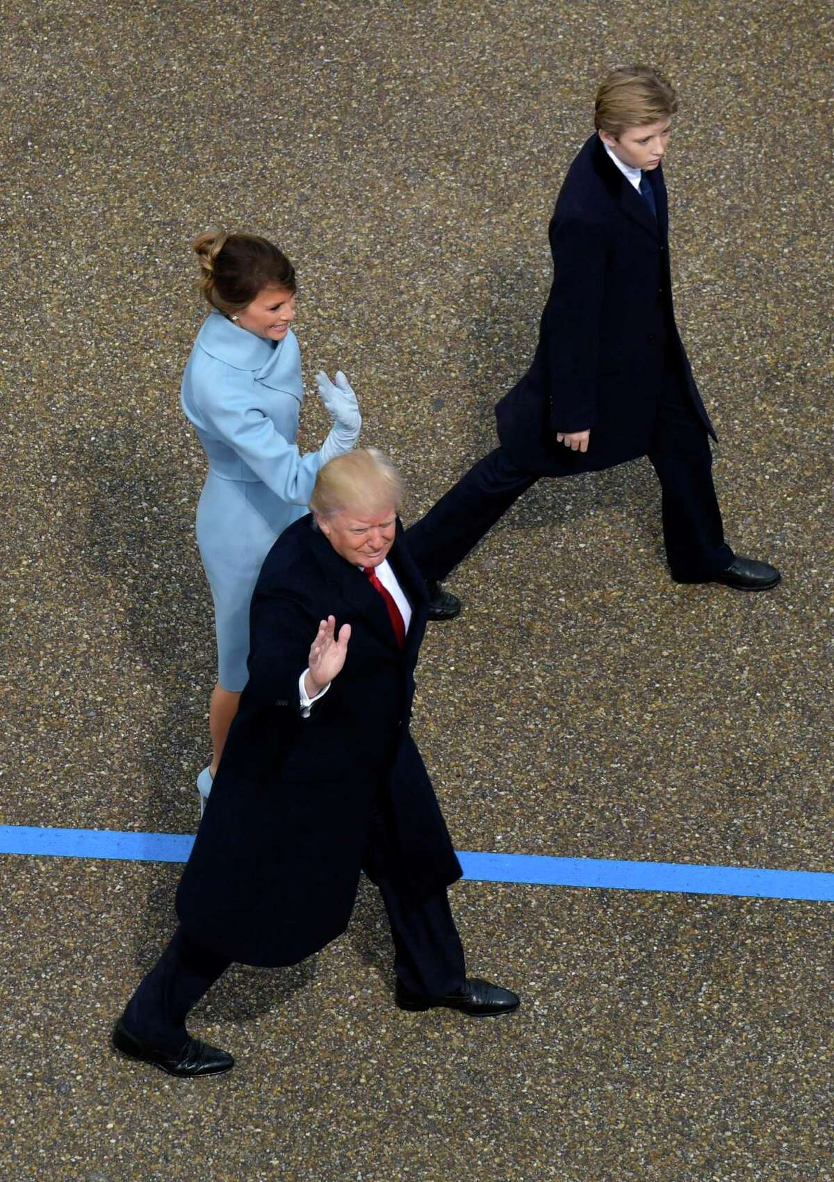 President Donald Trump waves as he walks with first lady Melania Trump and their son Barron during the 58th Presidential Inauguration parade for President Donald Trump in Washington. Friday, Jan. 20, 2017. (AP Photo/Susan Walsh)