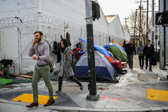 People walk past a tent encampment on Harrison Street in San Francisco, Calif., on Wednesday, January 11th, 2017.