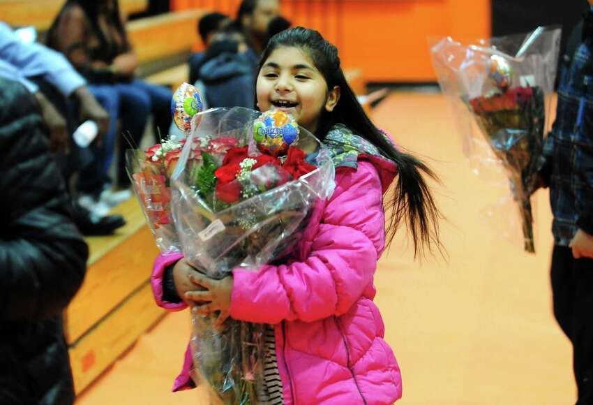 Rashi Verma, 7, carries two boquets of flowers as she arrives to watch her relative Class Valedictorian Sonam Verma duing the Class of 2017 LPN Program Graduation held at Bullard Havens High School in Bridgeport, Conn., on Friday June 20, 2017. Karen Ivers, the LPN (Licensed Practical Nursing) Department Head, has been with the program for more than 30 years at Bullard Havens and is retiring. This is also one of the final graduating classes of LPN's in the state run program.