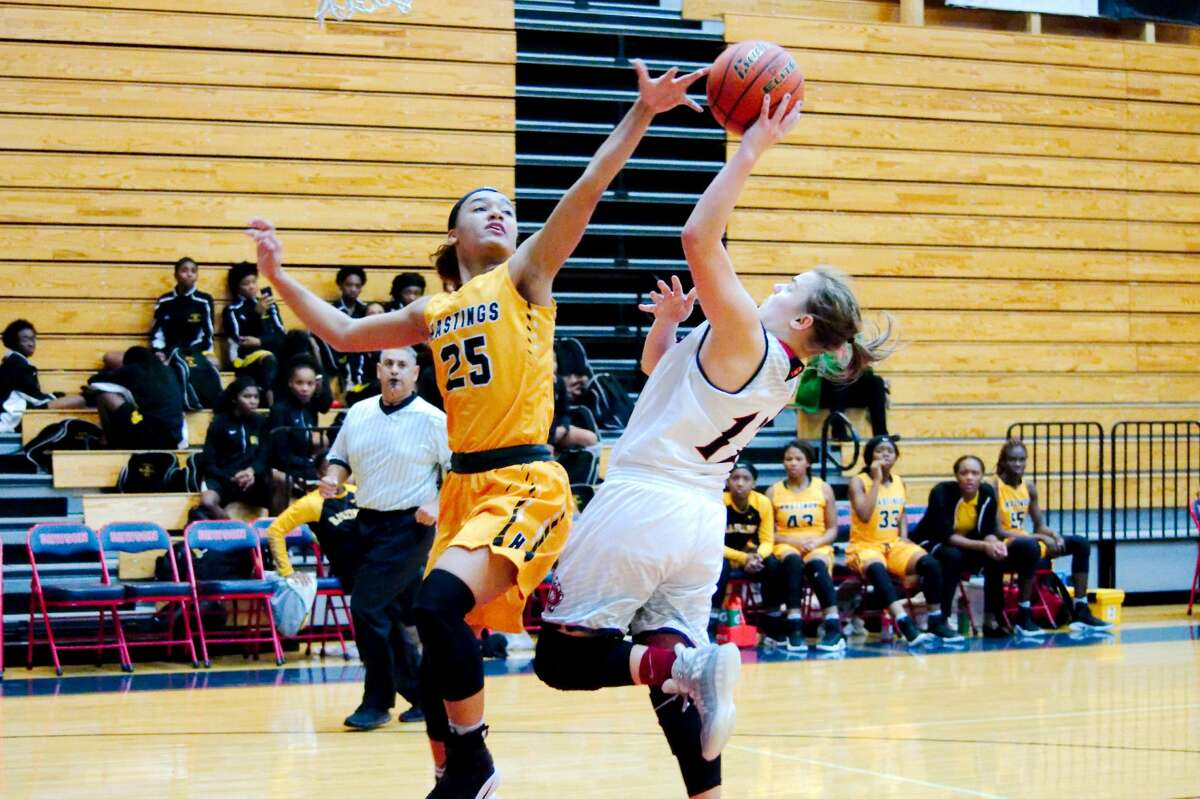 Dawson's Taylor Morris (14) tries to put up a shot over Hastings' Kai-Lee Valentine (25) Friday, Jan. 20 at Dawson High School