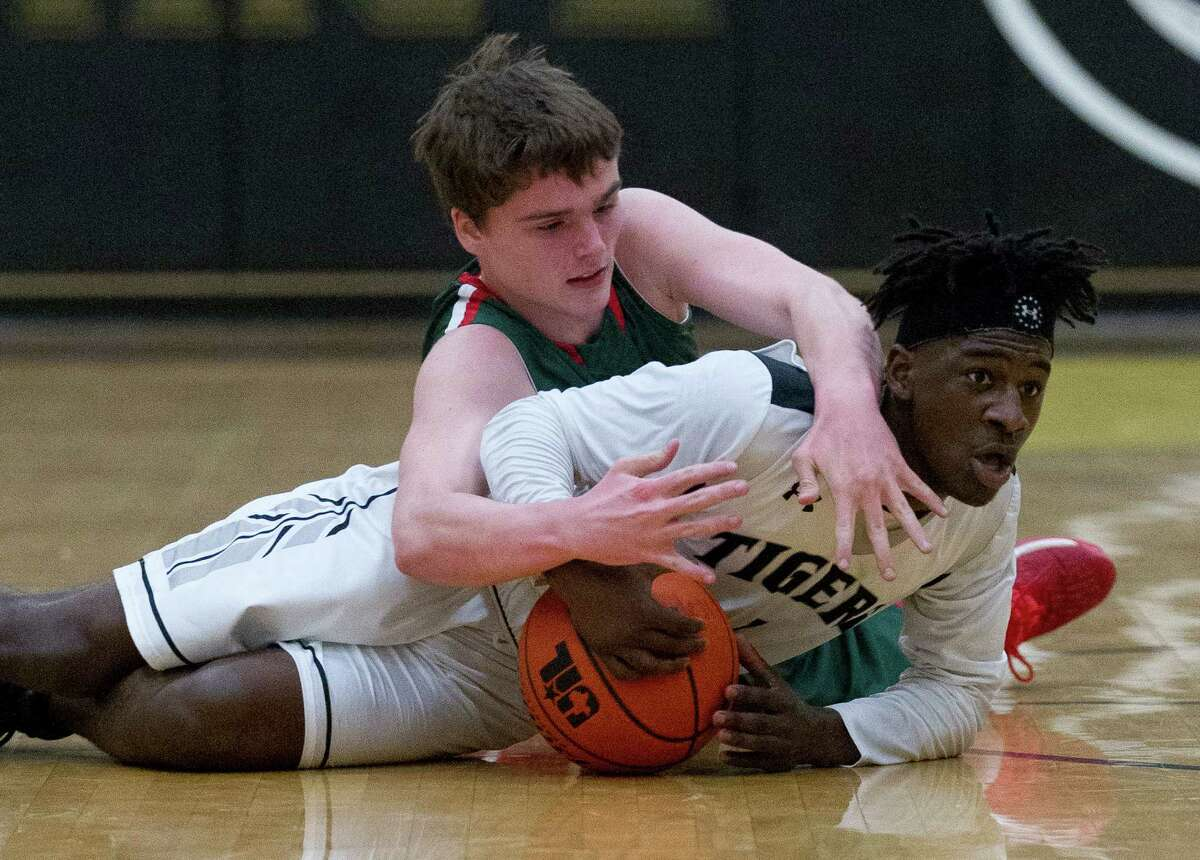 Conroe guard Jay Lewis looks to pass after diving on a loose ball against The Woodlands forward John Stubbs (10) during the first quarter of a District 16-6A high school boys basketball game at Conroe High School Friday, Jan. 20, 2017, in Conroe. Conroe defeated The Woodlands 74-71 in overtime for the Tigers' first win over the Highlanders since 2008.