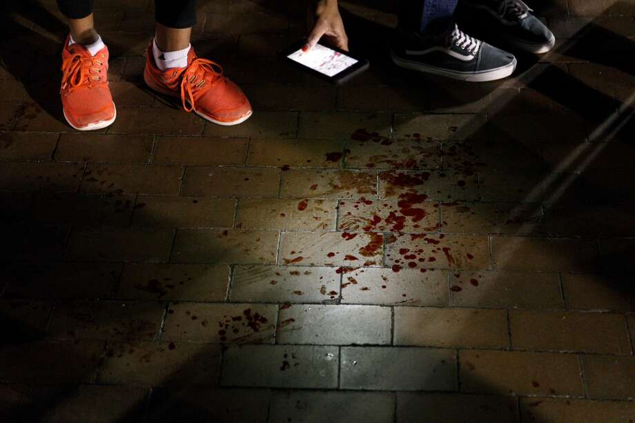 People photograph blood on the ground as a man is taken away by police following an injury during clashes between groups at Red Square on the University of Washington campus. Photo: GRANT HINDSLEY