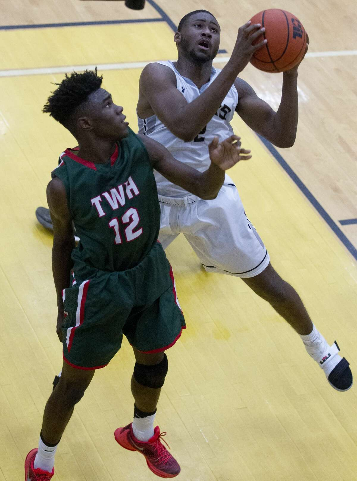 Conroe foward Quentin Brown (12) grabs a rebound over The Woodlands guard Kesean Carter (12) during the second quarter of a District 16-6A high school boys basketball game at Conroe High School Friday, Jan. 20, 2017, in Conroe. Conroe defeated The Woodlands 74-71 in overtime for the Tigers' first win over the Highlanders since 2008.