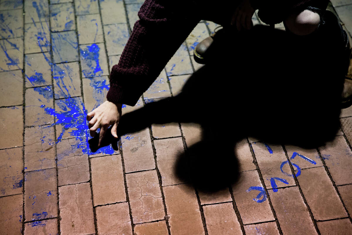 A protester takes paint from a paint-filled balloon and writes a message outside Breitbart.com editor Milo Yiannopoulos' speech at University of Washington on Friday, Jan. 20, 2016