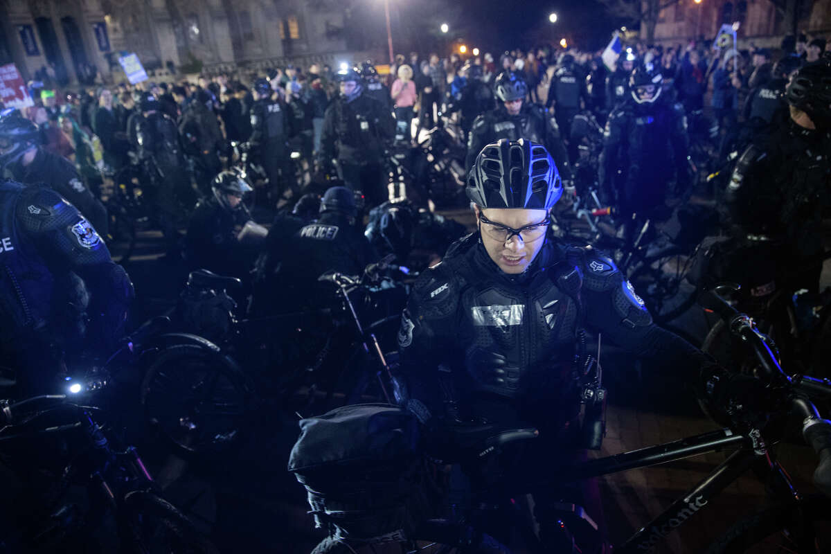 Police clear an area for a cart to escort the victim of a shooting out of the protest outside Breitbart.com editor Milo Yiannopoulos' speech at University of Washington on Friday, Jan. 20, 2016