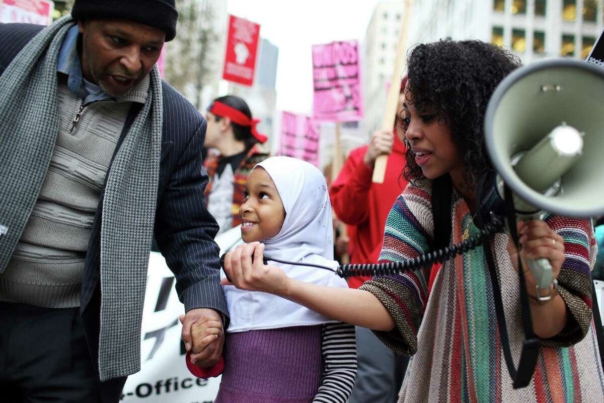 Sophia Tekola holds up the mega phone to Nuriya Robele, 8, who was marching in the immigrant rights demonstration with her father Ahmed. Ahmed, who moved to the United States from Ethiopia 25 years ago and is muslim, said this is the first time he has felt like his religion is not respected in this country. The march was in response to President Donald Trump's inauguration on Friday, Jan. 20, 2017.