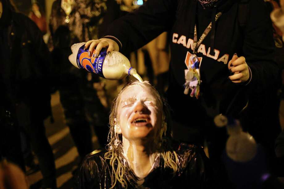 A young woman's eyes are washed out with milk after she is sprayed with pepper spray by police. Protesters and police clashed at the school as Milo Yiannopoulos spoke inside. One man in the crowd was shot as supporters and opponents of the Breitbart.com editor waited to see if they would be able to attend his talk there. Photo: GENNA MARTIN,  SEATTLEPI.COM / SEATTLEPI.COM