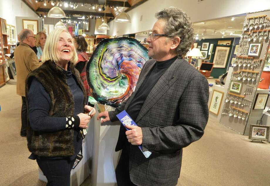 The Cultural Alliance of Fairfield County toured three art galleries in Norwalk, part of the Progressive Gallery Tour of Fairfield County, on Wednesday, Jan. 17, in Norwalk. Artists' Market owner Jeff Price talks with Lee Walther from Black Rock about the Robert Custer blown glass sculpture during the tour. Photo: Alex Von Kleydorff / Hearst Connecticut Media / Connecticut Post
