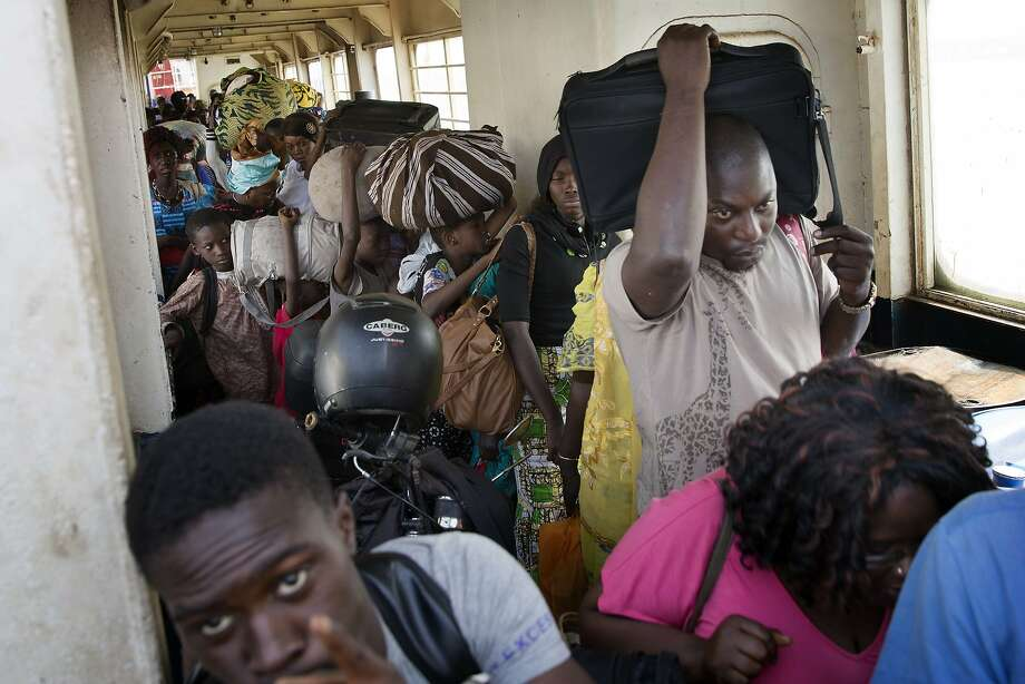 People wait to disembark from a ferry arriving at the port in Banjul, Gambia, Saturday Jan. 21, 2017, as life slowly returns to the Gambian capital.  Gambia's defeated leader Yahya Jammeh announced early Saturday he has decided to relinquish power, after hours of last-ditch talks with regional leaders and the threat by a regional military force to make him leave. (AP Photo/Jerome Delay) Photo: Jerome Delay, Associated Press