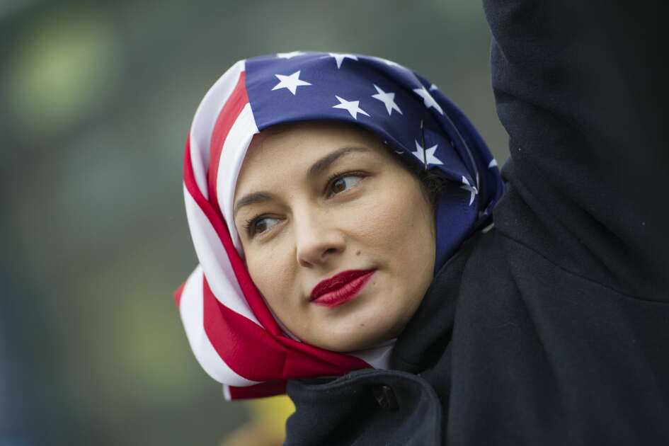 A woman wearing a USA flag as a headscarf attends a protest for women's rights and freedom in solidarity with the Women's March on Washington in front of the Brandenburg Gate on January 21, 2017 in Berlin, Germany. The Women's  March originated in Washington DC but soon spread to be a global march calling on all concerned citizens to stand up for equality, diversity and inclusion and for Women's  rights to be recognized around the world as human rights. Global marches are now being held, on the same day, across seven continents.