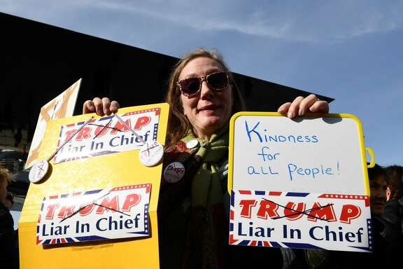 A protester holds placards reading 'Trump - Liar in Chief' and 'Kindness for all people' during a 'Women's March' organized by feminist and human rights groups in solidarity with women marching in Washington and around the world for their rights and against the reactionary politics of the newly sworn-in US President Donald Trump, at the Old Port (Vieux Port) of Marseille, southern France, on January 21, 2017.