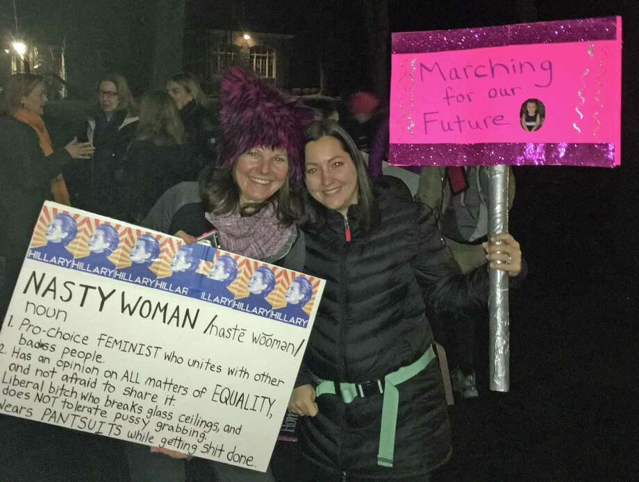 Colleen Morris, left, and Samantha Casella, right, of Darien, hold signs outside Second Congregational Church in Greenwich at 3:30 a.m. on Saturday, Jan. 21, 2017. Photo: Neil Vigdor /Hearst Connecticut Media