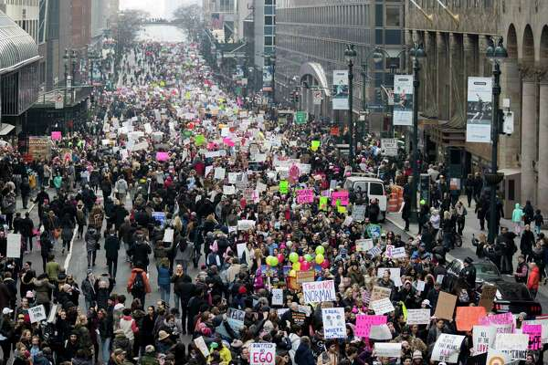 Demonstrators march across 42nd Street during a women's march, Saturday, Jan. 21, 2017, in New York.  The march is being held in solidarity with similar events taking place in Washington and around the nation.