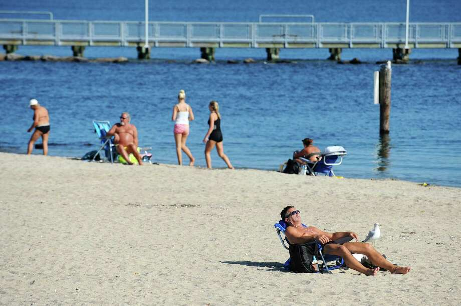 Folks soak up the sun at West Beach in Stamford, Conn. on Wednesday, Oct. 19, 2016. Wednesday was another unusually warm day for October with the temperature peaking in the low 80s while Thursday is expected to be more seasonal with a high near 65. Photo: Michael Cummo / Hearst Connecticut Media / Stamford Advocate