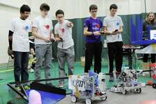 Greenwich High School robotics team members from left in white shirts, Rahul Subramaniam, 15, Calvin Hirsch, 16, and driver, Richie Consiglio, also 16, operate their robot 10877 during the 4th annual Gator Bowl Connecticut State First Tech Challenge Qualifier Robotics tournament at Greenwich Academy, Conn., Saturday, Jan. 21, 2017. Greenwich Academey science teacher Gail Sestito said 19 teams competed including the local Greenwich High School Robotics team. Sestito said the host team, the Greenwich Academy Robotics team, RoboEpic, as is customary, did not compete. Evan Barnet of First Tech Challenge said the tournament, through competition, hopes to expand the robotic and engineering opportunities for the students who take part.