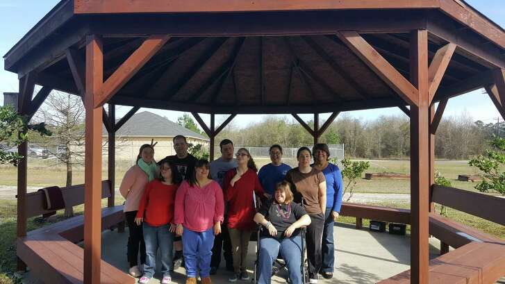 New Horizons patrons and staff pose for a photo under the pavilion beside their activity center in New Caney Jan. 20.
