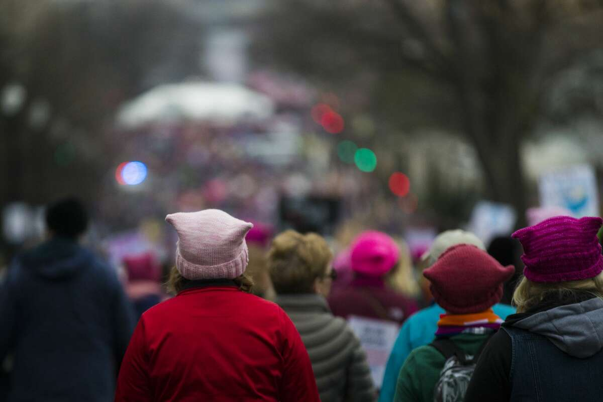 Demonstrators wearing pink pussycat knit hats walk to join other protestors to participate on the Women's March, Saturday, Jan. 21, 2017, in Washington D.C.. ( Marie D. De Jesus / Houston Chronicle )