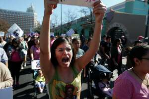 """Trinity student Olivia Garza shouts as she marches with about 1,200-1,500 people who gathered at City Hall on Saturday, Jan. 21, 2017 for San Antonio's version of the women's march happening in Washington, D.C. to oppose Donald Trump's inauguration. The march started in downtown and concluded at Estela's Mexican Restaurant on the city's Westside. Advertised as a march against """"hate, misogny, transphobia, homophobia, xenophobia,"""" the organizers and protestors railed against Trump's comments against women and minorities."""