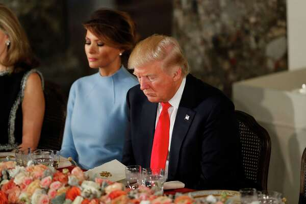 President Donald Trump and first lady Melania Trump bow their heads in prayer during the inaugural luncheon Friday in Washington, D.C.