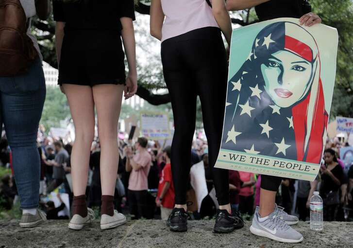 A marcher holds a poster made by Shepard Fairey while listening to speakers at Houston City Hall on Saturday, Jan. 21, 2017, in Houston.