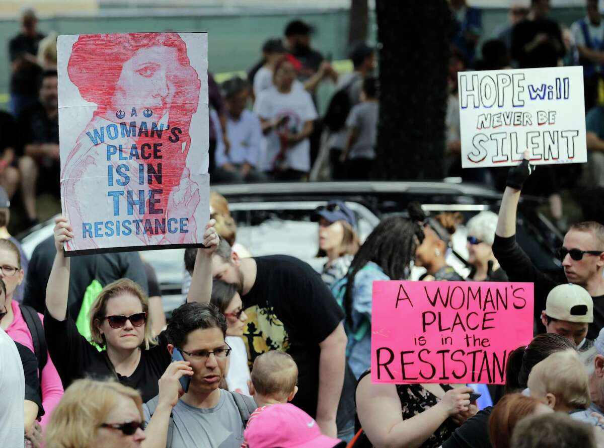 Attendees hold signs in the street at the Houston Women's March in Houston, TX on Saturday, January 21, 2017.