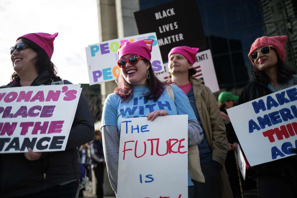 Women wear pink hats as they watch the WomenÕs March on Seattle pass by on 4th Ave on Saturday, Jan. 21, 2017.