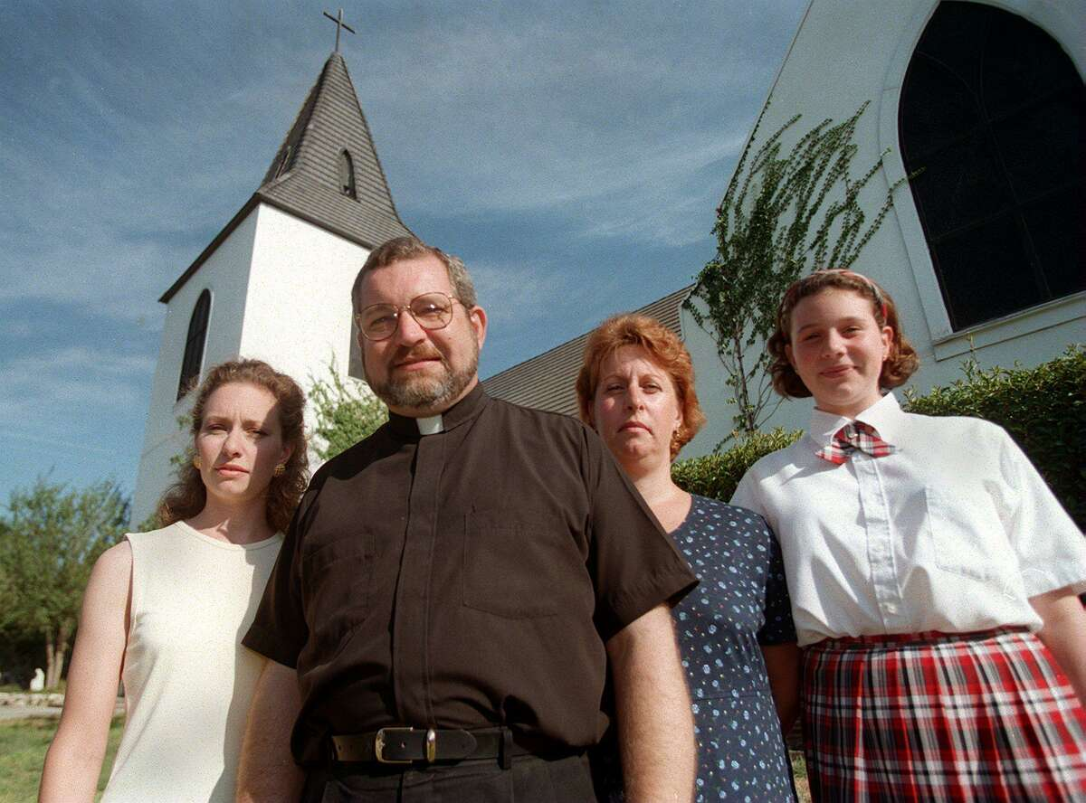 Father Christopher Phillips with his family at Our Lady of the Atonement Church. On the left is his daughter Christian and on the right are his wife Jo Ann and daughter Lurana, 11.