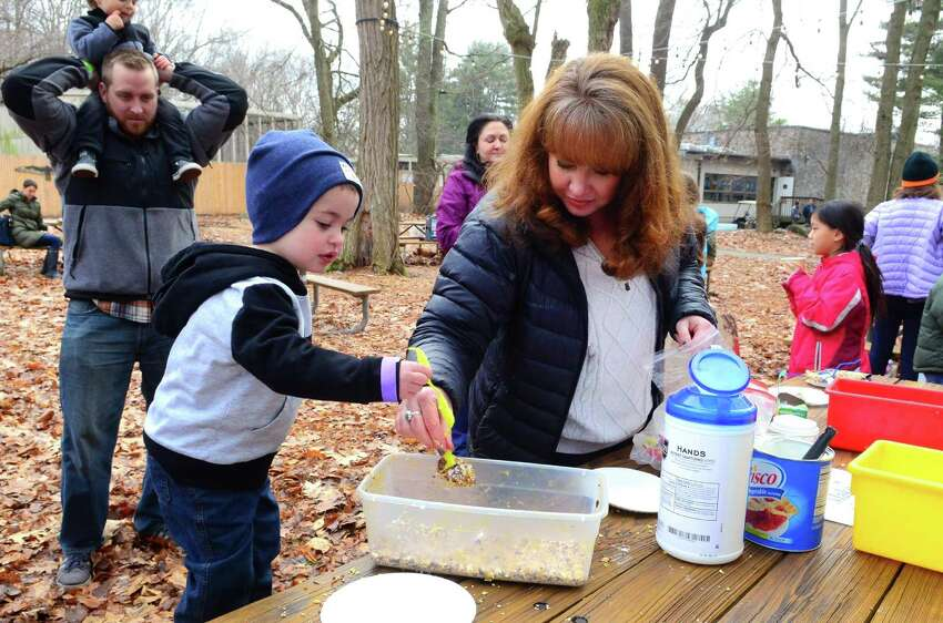 Mason Joyce, 2, of Trumbull, works on making a pine cone bird feeder with some help from Earthplace volunteer Elizabeth Carpenter during its Winterfest celebration in Westport, Conn., on Saturday Jan. 21, 2017. Children made pinecone birdfeeders, played with insta-snow, built mini ice sculptures, and many more amazing winter crafts. Indoor activities included exploring crystals under a microscope and hourly visits with various animals in the center's auditorium. Families were able to hike trails throughout the woods around the center and a campfire and hot chocolate greeted visitors as well.