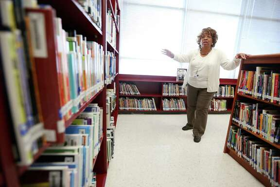Cullen Middle School librarian Janice Shaw surveys her new stocked shelves.