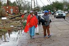 Residents of south Hattiesburg, Miss., survey the damage to their community following a early morning tornado blew through, Saturday, Jan. 21, 2017.  The tornado was part of a wall of stormy weather traveling across the region, bringing with it rain and unstable conditions.  (AP Photo/Rogelio V. Solis)