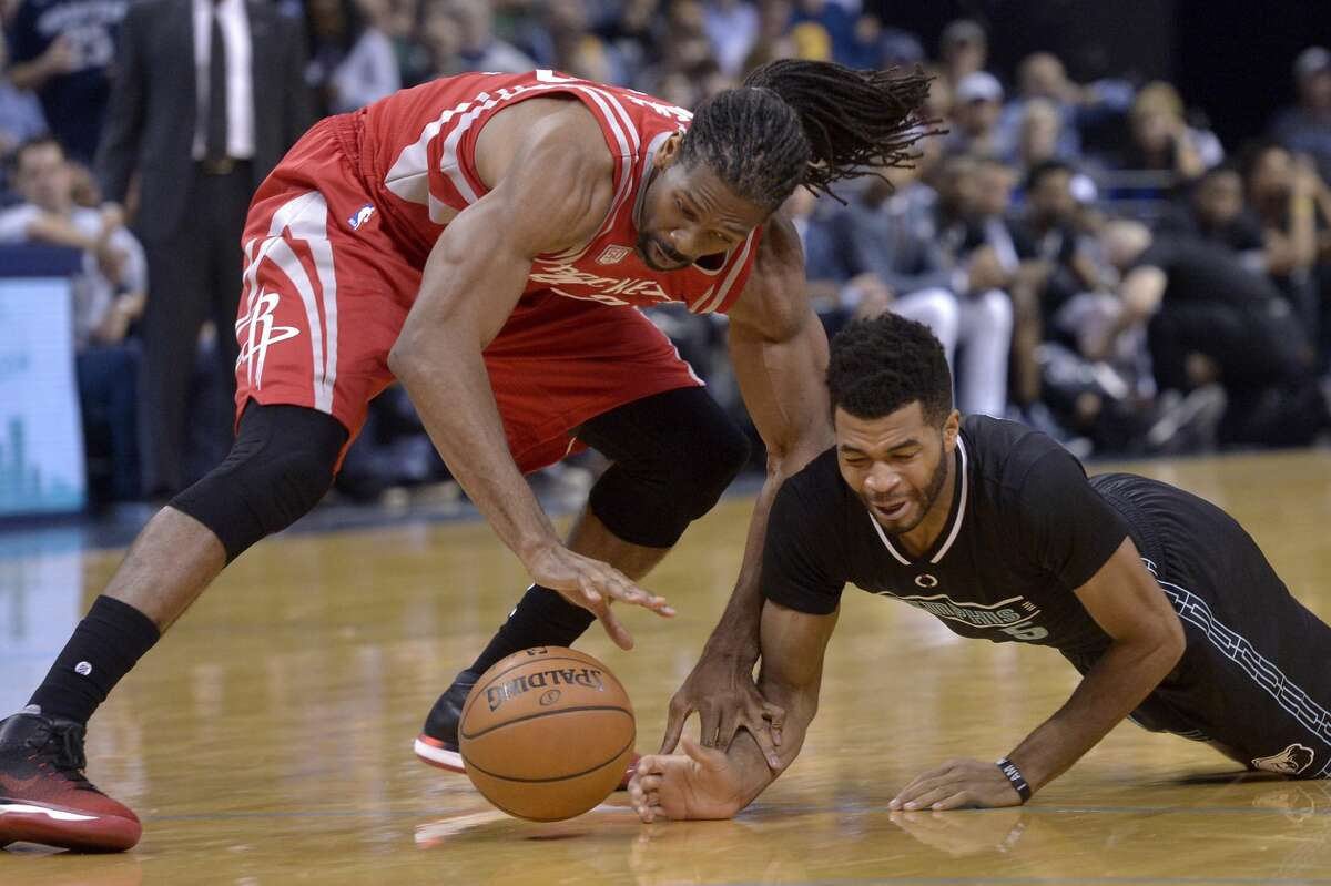Houston Rockets center Nenê, left, and Memphis Grizzlies guard Andrew Harrison (5) struggle for control of a loose ball in the second half of an NBA basketball game Saturday, Jan. 21, 2017, in Memphis, Tenn. (AP Photo/Brandon Dill)