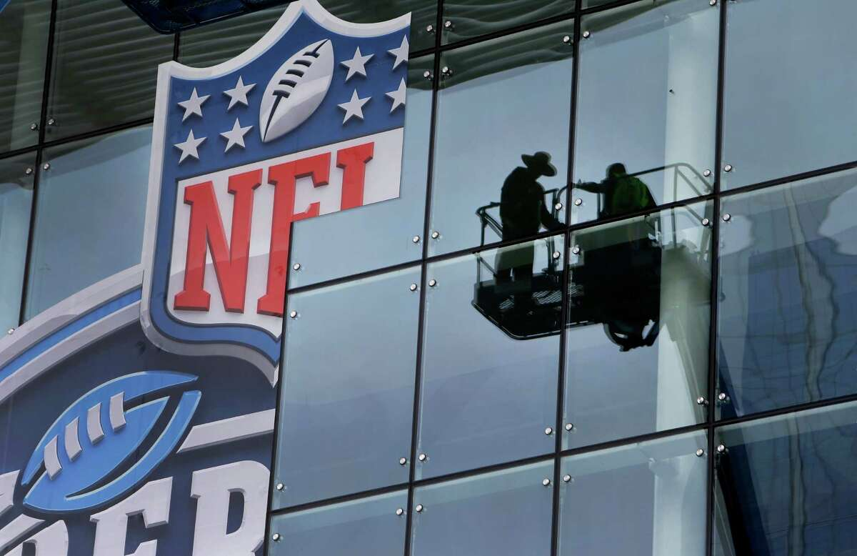 Workers prepare a sign outside the George R. Brown Convention Center, one of the hundreds of venues in the Houston area booked for Super Bowl events.