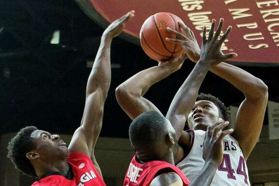 Texas A&M's Robert Williams, right, shoots through a sea of arms provided by Georgia's Jordan Harris, left, and Derek Ogbeide during SEC action Saturday.