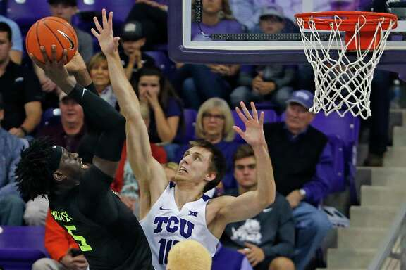 Baylor's Johnathan Motley, left, shoots over TCU's Vladimir Brodziansky to produce two of his 15 points during Saturday night's victory in Fort Worth.